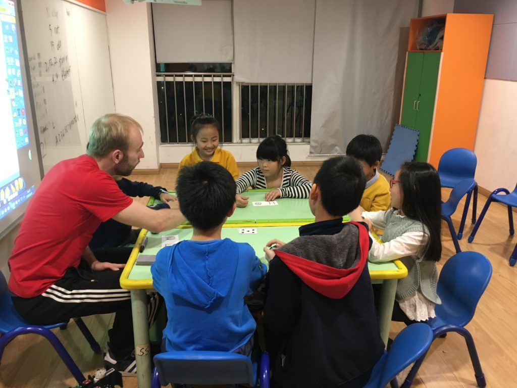 Teacher Richard siting around a table with his TEFL students at First Leap English